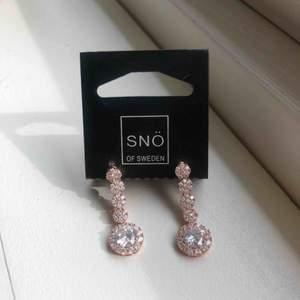 Säljer dessa oanvända örhängen från Snö of Sweden. Rosé och silver. Längen är cirka 3,5 cm