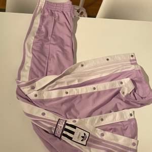 Ljus lila Adidasbyxor med slits på sidorna.