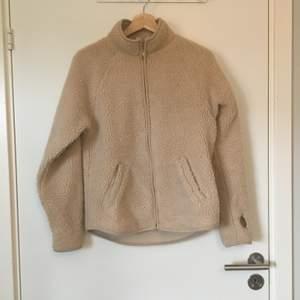 Beige fleece/teddy-jacka från Monki. Stl XXS, stor i storlek. Gott skick. Frakt betalas av köparen.