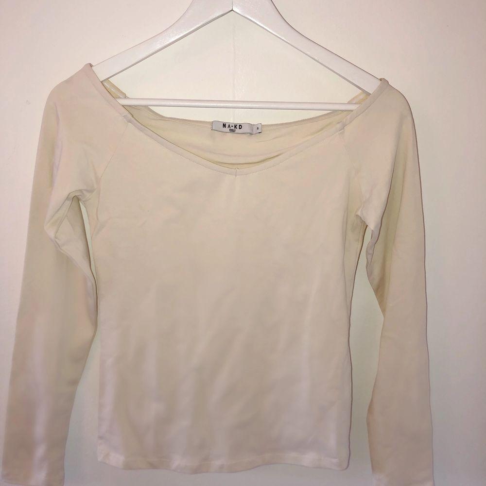 Oanvänd tröja från NaKd. Tröjan är benvit och är nästan off-shoulder. Supersmickrande urringning. Perfekt som basic! Jag köpte den för 100 kronor och säljer för 40🥰. Skjortor.
