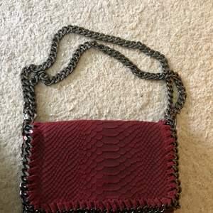 Vinröd väska med alligator imitation. Mocka material. Den har långa band egentligen men man kan fixa så de blir kortare som på bilden!