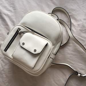 Liten vit/svart ryggsäck från Stradivarius. Endast använd en gång så den är som ny. Nypris 250, säljer för 120.