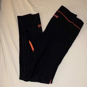 Träningsbyxor / träningstights från Casall i svart med rosa detaljer. I nyskick, oanvända. Size: 36 (small)