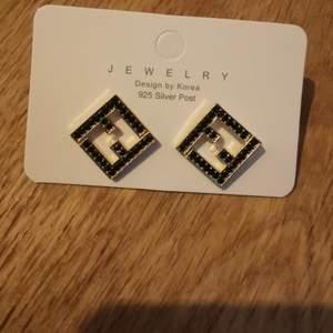 Snygga Fendi inspirerade örhängen. Guld med svarta stenar. Nickelfria.