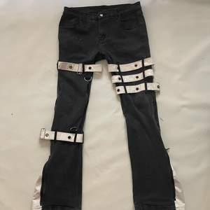 Svrta bootcut byxor med vita läder spännen runt om, där det är bootcut kan man dra ner en dragkedja och där finns det vitt läder de. Så snygaaaaa.