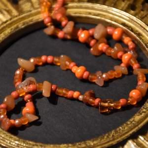 Ett halsband med röd aventurin och orangea pärlor.