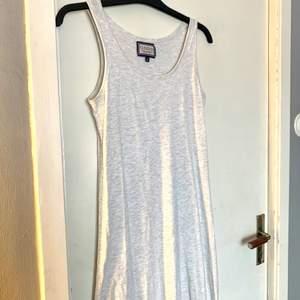 En basic ljusgrå maxiklänning. Rak i modellen men skulle säga att den är ganska figurnära när den sitter på. Använd ca två gånger. Fin klänning i fint skick🙂