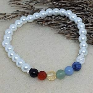 Ett pärlarmband med en pärla för varje chakra. Chakrastenarna är bergskristall, sodalit, angelit, aventurin, citrin, karneol, obsidian. Runtom är det vanliga vita glaspärlor ❤️