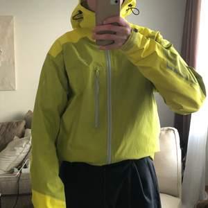 Arcteryx jacka i storlek Medium. En väldigt fet jacka i gul färg som är justerbar. Jackan har endast en ficka. Den är vattentät. Det som gömmer spännet har släppt. Nytvättad. Storlek Medium.