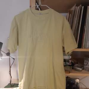Retro tisha med chanelmärke. Troligen inte riktigt.väl använd. Mer citrongul/ ljust gul än på bilderna! En oversize small men går från xs till L beroende på hur man vill ha det!