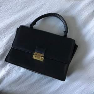 En extremt gullig miniväska, som en liten portfölj. Lite slitage syns utanpå.