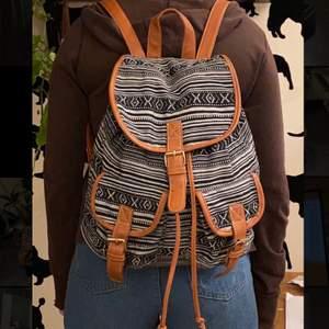 """Mönstrad ryggsäck med bruna konstskinns och guld detaljer. Två små fack på utsidan som stängs med magnetknappar. En ficka på baksidan (mot ryggen) som stängs med dragkedja. En likadan ficka med dragkedja på insidan av ryggsäcken samt två mindre fack på insidan av ryggsäcken. Ryggsäcken snöras ihop med en konstskinnsrämm och sedan med ett """"lock"""" som stängs med magnetknapp. Rämmarna är justerbara.  Mått: Höjd- ca 30-35cm Brädd- ca 32cm Djup- ca 17cm  Frakt tillkommer"""