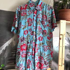 Blommönstrad herrskjorta i strl L. (Står XL i men uppfattar den som mindre). Härliga färger och fint skick!