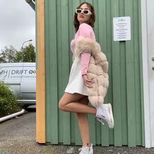 long length faux fur gilet in blush pink.