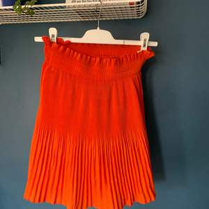 Plisserad kjol i jättefin röd/orange färg, märke och storlek saknas men den är väldigt stretchig så uppskattar att den skulle passa bäst en XS/S. Slutar strax innan knät på mig som är 175.