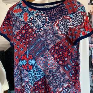 Röd/blå, mönstrad T-shirt. Normal passform och fint skick!