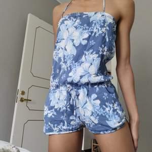 En söt blå pösig bodysuit till försäljning som passar jätte bra inför sommaren. Den är blommig och har även fickor vilket är alltid skönt. 💞 Pma gärna vid frågor!