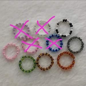 Egen gjorda ringar, det finns fler av varje färg.                             En blå, grön, svart vit, brun, röd, rosa vit, lila vit, rosa lila, perl vit. Det går även att beställa specific färg och storlek!  Storlekarna är olika men mellan s-m. Om man är intreserad så är det enkelt att få måten till alla ringar för att se om ringarna kommer passa. Dem kostar 10kr st!😇 dem som är överkrysade är sålda!