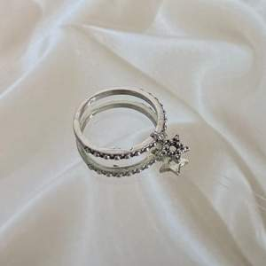En ring med en stjärna hängandes. I färgen silver. Swipe för att se hur den sitter på. Frakt på 12 kr tillkommer, men köper du 3 stycken eller fler är frakten gratis. Hör av er vid intresse eller om ni vill ha fler bilder! 🤎
