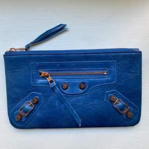 Liten Balenciaga (ej äkta) inspirerad kuvertväska/plånbok. Aldrig använts och i äkta läder. En tråd som är lite lös framtill (se bild 2) därav lågt pris. Mått: 20x12 cm
