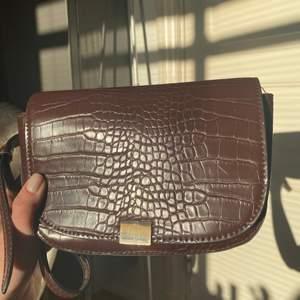 """brun väska från mango med justerbara band. egentligen gjord för att ha som """"skärp"""" i midjan alltså typ en midjeväska men jag har använt den som axelväska vilket även det funkar! inga repor eller liknande"""