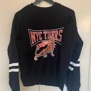 En svart tröja från Gina Tricot med tryck och hål, använd fåtal gånger!