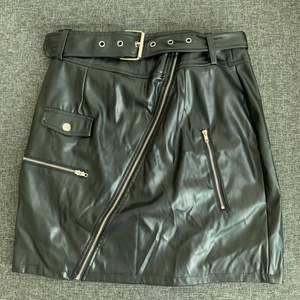 Svart kjol i imitationsskinn från Prettylittlething i strl 38 (M) med dragkedjor som detaljer. Använd vid ett tillfälle, så i mycket bra skick.