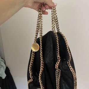 En äkta Stella väska i guld och svart. Köpt för 3 år sedan i Stella butiken. Använd ett fåtal gånger. Perfekt skick. Inga defekter. Köpt för 8500kr. Dustbag finns kvar