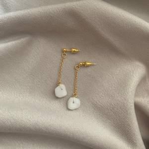 guldiga örhängen med kedja och marmorstenar