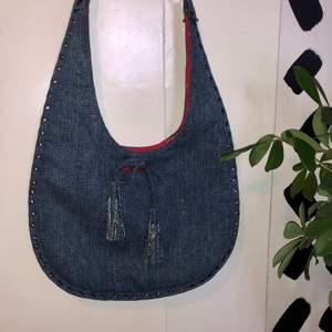 En snygg y2k denimväska från Hot Kiss. Väskan har rött innertyg och coola studs och metalldetaljer. Mått: ca 30x40cm+handtag. ❗️Köparen står för frakten❗️Fråga om du har några funderingar🌸🌟