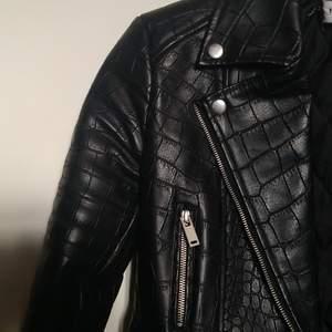 Svart skinnjacka i fake läder från Nelly.com. Ormliknande mönster och med snygga silverdetaljer. Använd fåtal gånger.