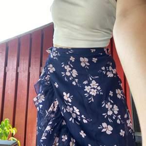 Blommig lite längre kjol som man knyter på sidan. Så himla fin att ha på sommaren!! Den är köpt från Nelly, märket är vero moda. Använt väldigt få gånger så den är som i nyskick!💗 Storlek XS men passar även större storlekar. Nypris 300 kronor.