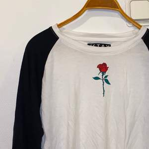Långärmad tröja med en ros på bröstet som detalj. Longfit. Använd ca 5/6 gånger. Storlek L men passar perfekt på storlek M då den är lite tajt i storleken.