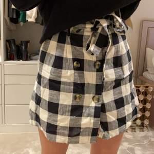 Jättefin rutig kjol med små knappar och ett bälte. Stolek 34