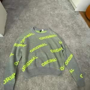 """En grå stickad tröja där det står """"original"""" i neon gul färg, tröjan har använts en gång därför säljer jag den"""