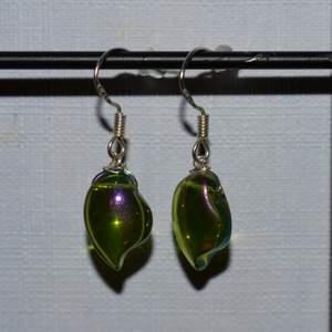 Handgjorda örhängen med gröna glaspärlor. Älskar färgen som ändras lite beroende på ljuset. De görs vid beställning och är därmed helt oanvända. Krokarna är gjord av äkta silver. Kolla gärna in min profil för fler handgjorda örhängen :))