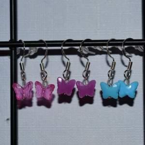 Handgjorda örhängen med små söta fjärilar. De finns i rosa, lila och blå. De görs vid beställning och är därmed helt oanvända. Krokarna är gjord av äkta silver. Kolla gärna in min profil för fler handgjorda örhängen :))