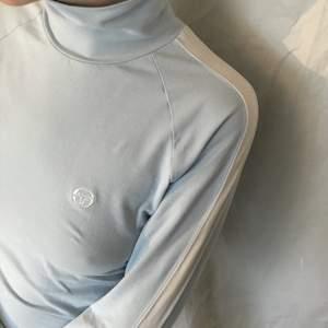 Så cool vintage turtleneck i ljusblått och vitt från märket Sergio tacchini. Långärmad med vita detaljer på armarna. Mjukt stretchigt bomullstyg, I princip nyskick.Går att vika upp som på bild ett eller ha instoppat i typ en vit tenniskjol eller med jeans. Färgen är närmast bild 2!!