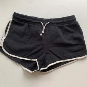 Svarta shorts med vit kant. Vita och guldiga snören i midjan och fickor på sidorna. Stl 146/152 från Lindex. Fint skick och skönt material. Byxorna kostar 20 kr, frakt ingår ej. Swipe för fler bilder.