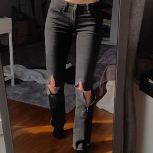 Lågmidjade grå/ svarta jeans med egengjorda hål på knäna. Supersnygga och perfekta till vår/ sommar! Superstretchiga och långa i benen! På mig som är 169 når de ner till marken. Byxorna har två små hål som knappt syns vid hällorna (se bild 3)