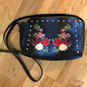 Svart väska i fejkskinn med nitar och blombroderier. Ca 27 cm bred. Aldrig använd.