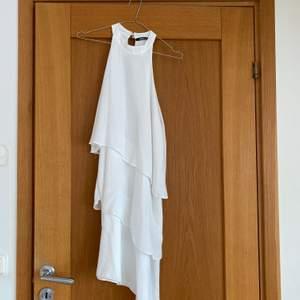 Vit fin klänning från Gina Tricot med volanger.