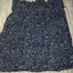 """Blå kjol från shein med blommor och ett """"skärp"""" i midjan så du kan justera själv hur tajt den ska sitta. Även resår så den sitter skönt. Den är rätt tunn men superskönt material, inte genomskinlig. Aldrig använd"""