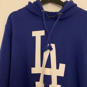 Blå hoodie med LA-tryck. Aldrig använd. Köpt på Stadium. Storlek L.
