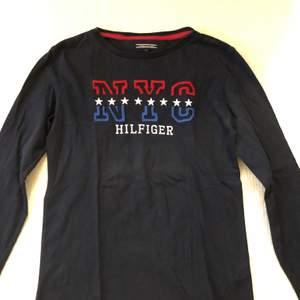 En fin Tommy hilfiger långärmad T-shirt i strl 164 navy färgad. Använd ett fåtal gånger, gott skick och felfri! Nypris: 600kr