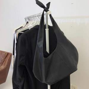 """Svart """"skinn"""" väska som man kan reglera längden själv genom att knyta! Rymmer mkt och är använd fåtal gånger🤍nyskick! Slutsåld på hemsidan"""