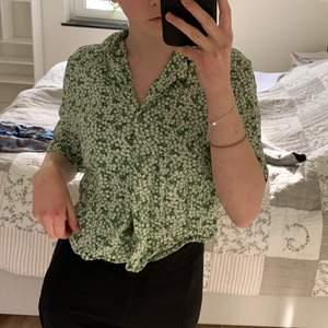 En grön tröjskjorta med vita små blommor🤍