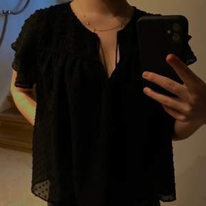 En svart blus från Zara i storlek M - passar även en S. Swipea för bättre ljus där man ser materialet och mönstret bättre!