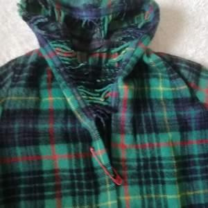 Supersnygg grönrutig filtjacka med röd säkerhetsnål, två fickor och luva, pingvinärmar. Mycket bra skick. One of a kind