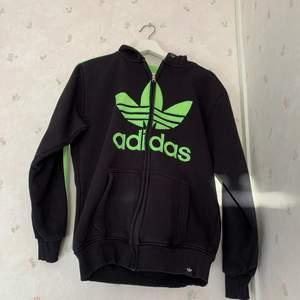 En svart Adidas kofta med neon gröna streck, passar alla både tjejer och killar, storleken varierar mellan S-XL beroende på hur du vill att den ska sitta!
